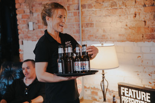 A waitress delivers beer  at The Manor House during a southern Colorado foothills wedding.
