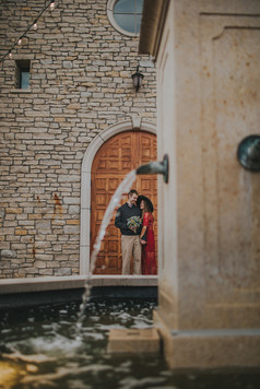 A couple stands in front of a large wooden door at Villa Bellezza