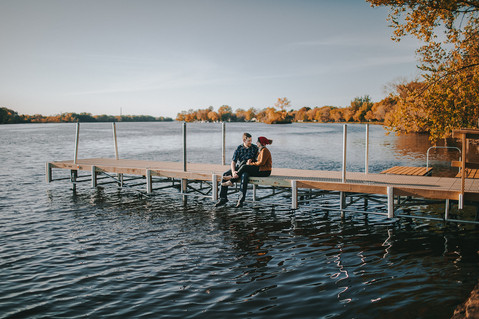 A man and woman sit on a dock on the Wisconsin River during a Wisconsin engagement session