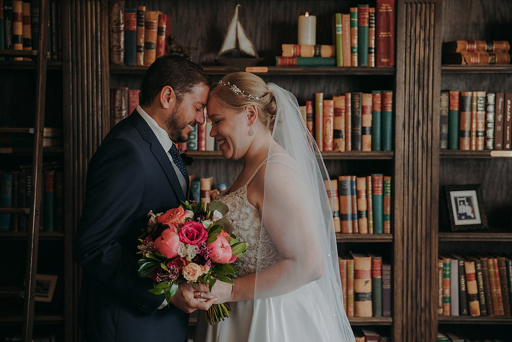 A man and women laugh together as they touch foreheads over the bridal bouquet in a library space of The Manor House during their southern Colorado foothills wedding.