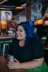 A women with blue hair smiling at at I/O Arcade Bar in Madison Wisconsin