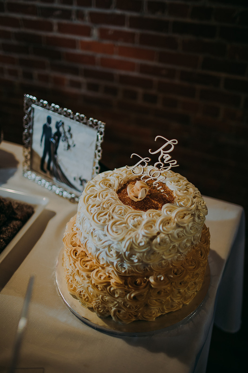 Handmade wedding cake with cream and gold rosettes