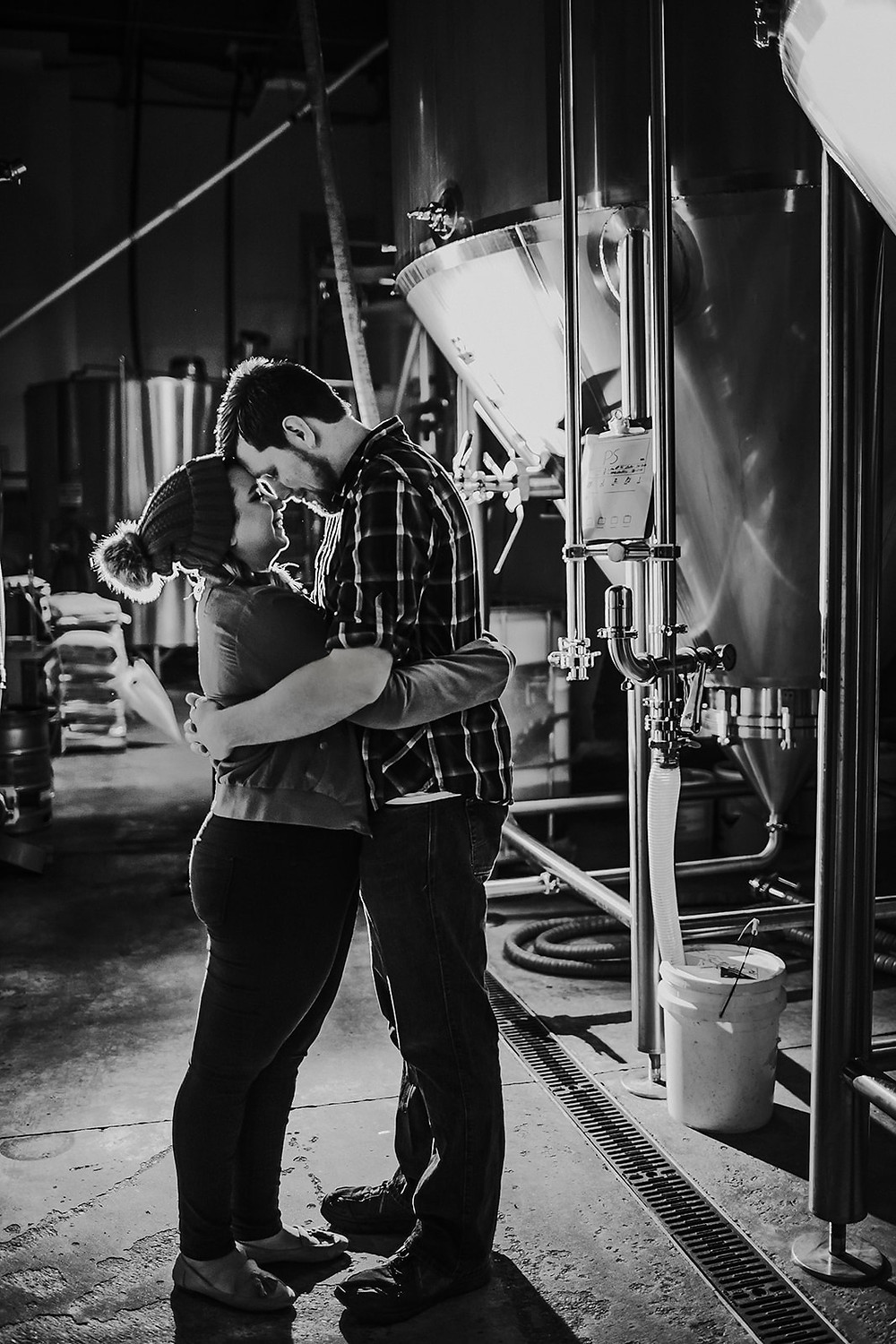 Man and woman touch foreheads inside O'so Brewery engagement photos
