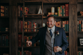A groom smiles while leaning on a bookshelf
