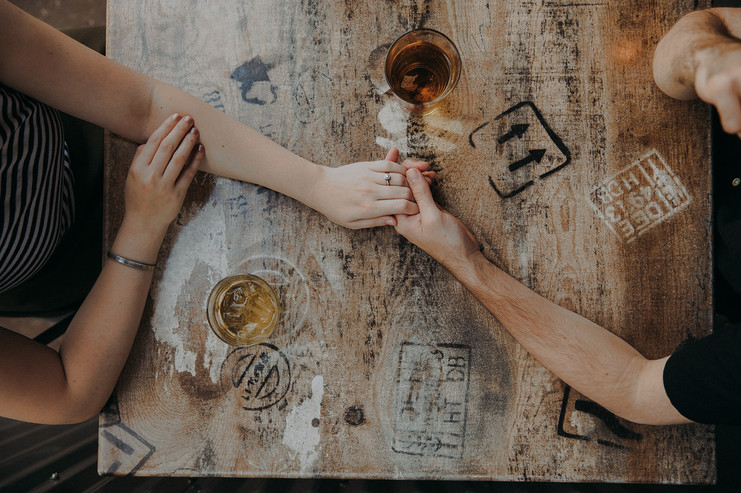 A man and women hold hands as they share drinks at Guu's on Main in Downtown Stevens Point