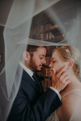 A bride and groom under a veil in a romantic embrace