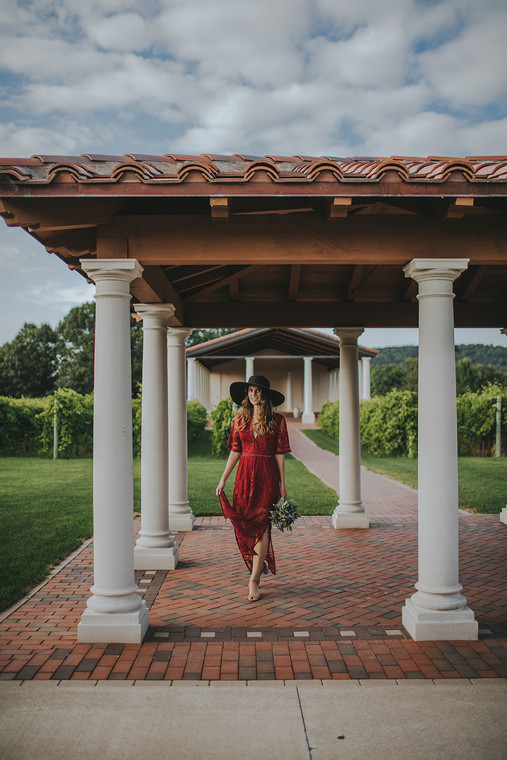 Women poses in a wine red dress at Villa Bellezza.