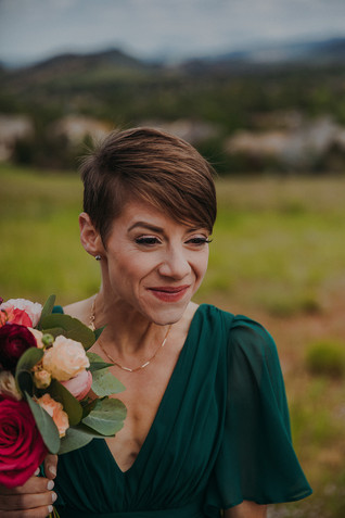 A bride smiles while holding peach roses