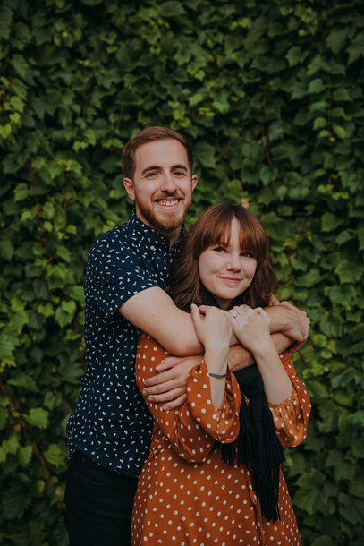 A man and women embrace in a hug in front of an ivy covered wall in Downtown Stevens Point