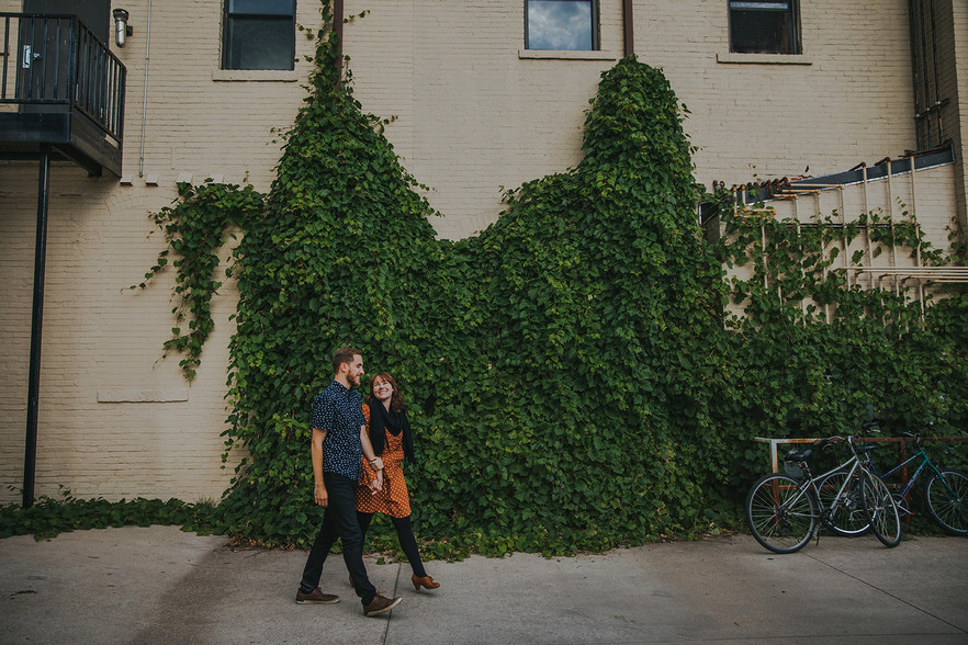 a man and women walked together in front of an ivy covered wall in Downtown Stevens Point