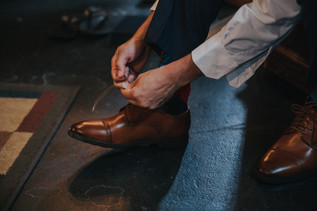 A man ties his brown leather shoes