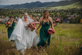 A bride and bridesmaids walk while laughing in a field