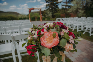 Peach roses in front of chair set up for a ceremony
