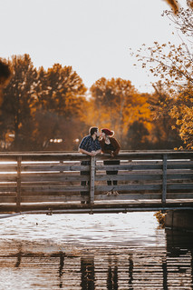 Man and a women kiss each other on a bridge in Pfiffner Park