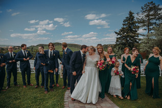 A bride and groom touch foreheads as they walk in front of their bridal party at The Manor House during a southern Colorado foothills wedding.