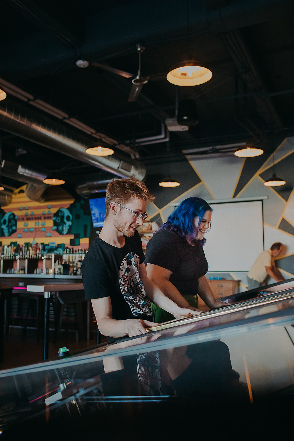 Couple plays pinball at the I/O Arcade and bar