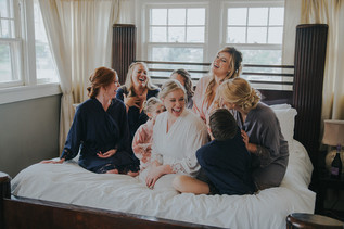 The bride and bridesmaids laughing together on a bed  The Manor House during a southern Colorado foothills wedding.