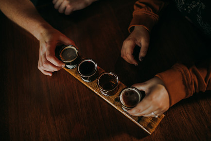 A close up of a man and woman selecting their tasters from a beer float at O'so Brewing Company