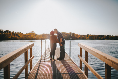 Man and a women kiss on a dock in Pfiffner Park engagement session