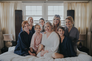 The bride and bridesmaids smile for the camera  The Manor House during a southern Colorado foothills wedding.