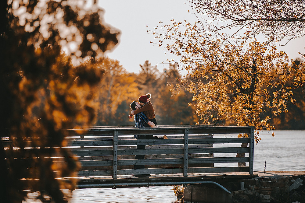 Couple kiss on a bridge in Pfiffner Park engagement session