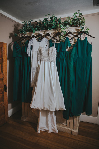 The wedding gown and emerald bridesmaids dresses  The Manor House during a southern Colorado foothills wedding.