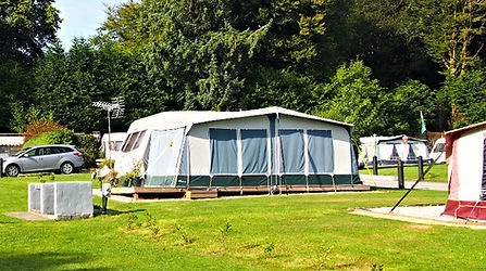A Caravan with awning on a green grass pitch
