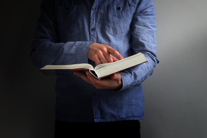 Man holding reading Bible