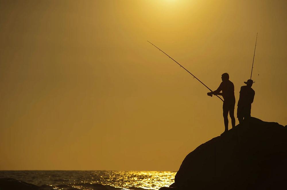 fishermen fishing from a rock