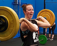 Coach & Personal Trainer, Sarah Hannay, holds a barbell while smiling at the camera