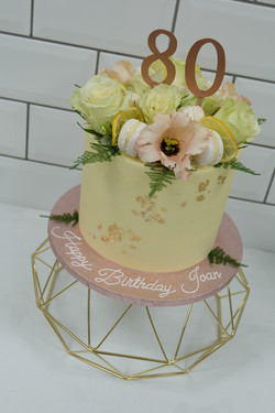 Flower, macaron, lemon and gold leaf cak