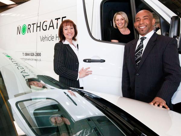 Three sales staff smiling with branded van at van hire company