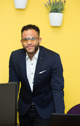 Business portait of a mixed race male against a yellow background