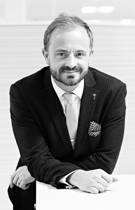 Black and white portrait of male solicitor leaning on worktop