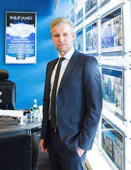 Business portrait of a male estate agent wearing a white shirt and blue suit taken in the office