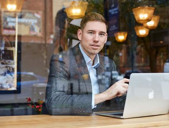 Portrait of a professional male wearing a suite working on a laptop taken through a window