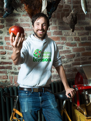 PR portrait of a male holding a large red apple towards the camera
