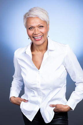 Business portrait of a mixed race female aged mid fifties wearing a white shirt with black jeans against a blue backdrop