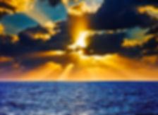 sunset over the ocean, golden sunset, deep blue ocean, golden rays through clouds