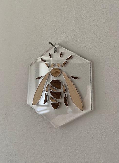 Photo d'une abeille en marqueterie de bois sur plexiglas, objet design pour la décoration et fabriqué à Paris.