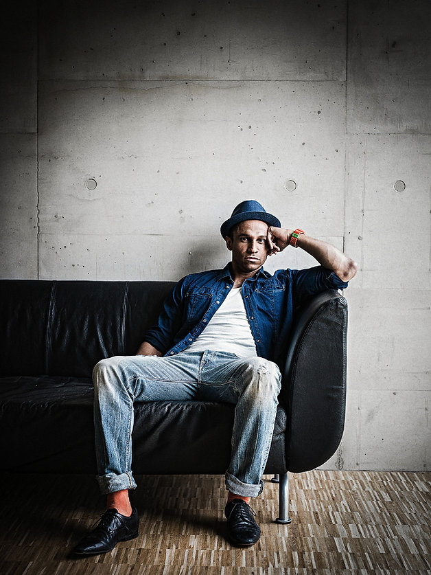 Imgaeshooting mit Daniel Aminati auf Sofa vor Betonwand
