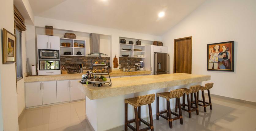cocina abierta con piedra natural e isla de gran tamaño
