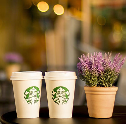 Imagem de dois copos de café da Starbucks em cima de uma mesa na página de vendas do curso online sobre branding ou gestão de marcas