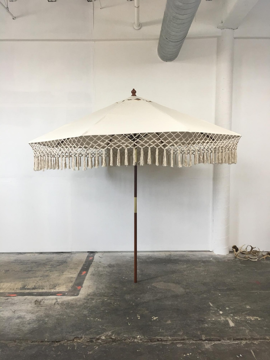Beige Umbrella with teak wood stand.