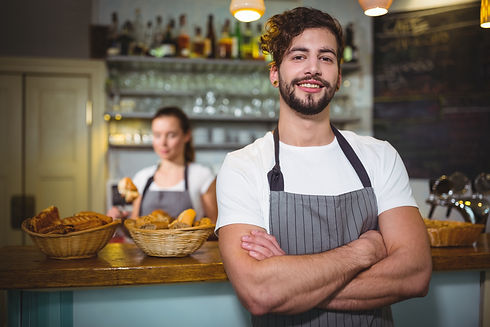 smiling-waiter-standing-with-arms-crosse