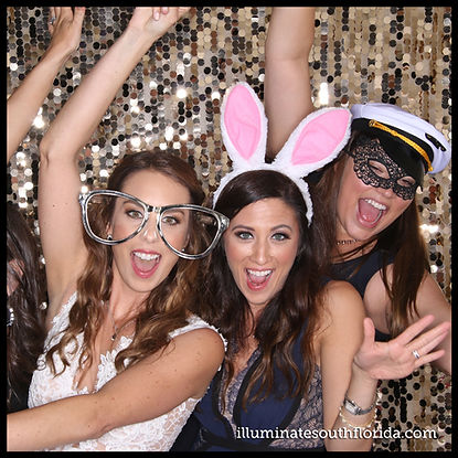 Beautiful bride having photo booth fun with her friends at her gorgeous wedding in Palm Beach County, Florida.  Photo Booth rental service provided by ILLUMINATE South Florida in Fort Lauderdale, Broward County.