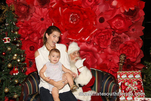 Fun with Santa in open style photo booth with custom flower wall backdrop during holiday school family festival in Fort Lauderdale, Broward County.  Photo booth service provided by ILLUMINATE South Florida