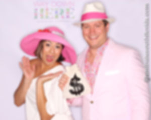Couple playing with photo booth props at theme party in Hollywoood, Broward County, South Florida.  Marketing and social media reach for corporate sponsor with custom backdrop