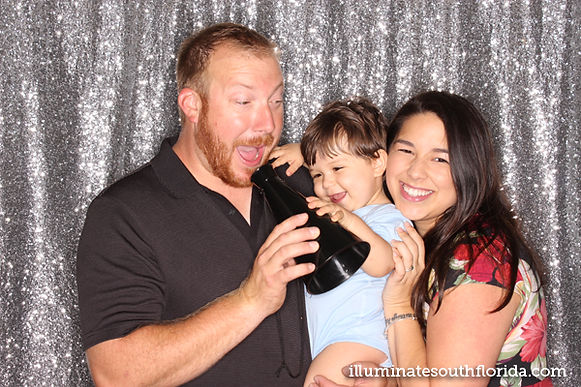 The photo booth provides the best party entertainment for birthday parties to celebrate all ages.  This one year old and his parents had fun with the photo booth props in Lauderdale-by-the-Sea, Broward County, Florida