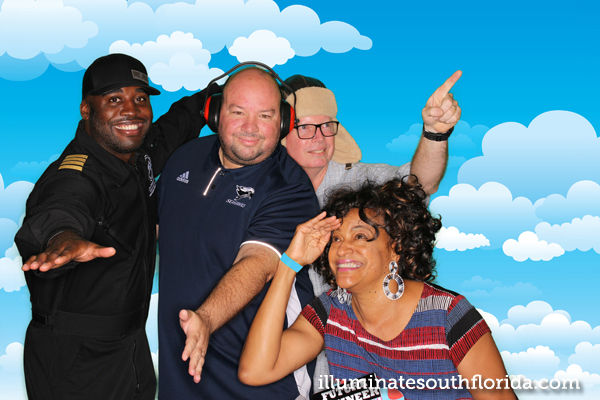 Tracy Cloyd of Miami's Hot 105 and Captain Barrington Irving have fun in green screen photo booth that allows choice of digital backgrounds at non-profit STEM Fest event for kids sponsored by Broward County Public Schools, Broward College, and the Flying Classroom in Pembroke Pines, Florida